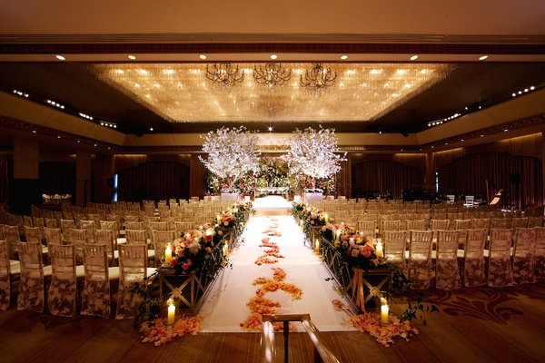 Indoor wedding with lace chair covers and petals