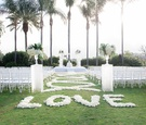 Grass lawn wedding ceremony white flowers and green leaves white flower petal swirl aisle love