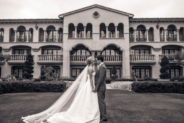 Black and white photo of bride and groom in front of grand del mar in san diego california wedding