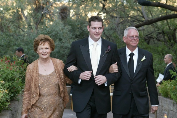 Groom and parents walking down aisle