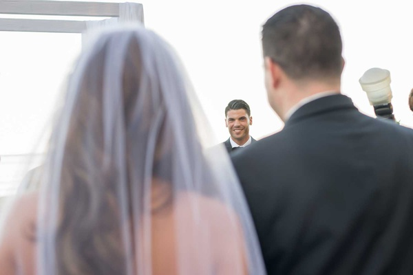 Bride in veil long brunette hair groom at altar looking at bride for first time