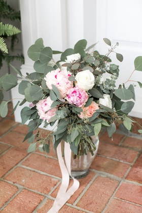 Clear vase tied with ribbon filled with pink peony pink garden rose white rose eucalyptus leaves