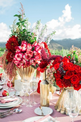 red and dark purple flower floral arrangements in gold vases with pink table linens vineyard setting