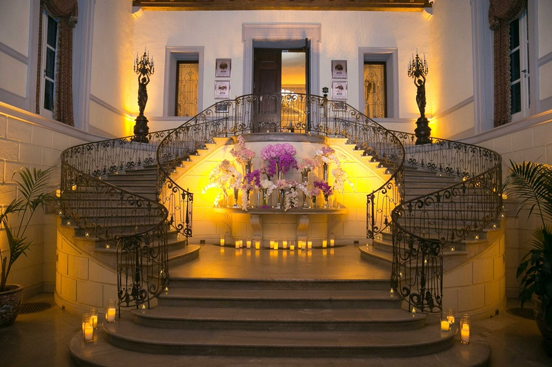 Grand staircase at Oheka Castle with pink and purple flower arrangements in center yellow lighting