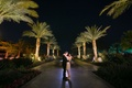 Bride in short second wedding dress with groom in suit looking into each other's eyes at resort