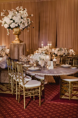 wedding reception mirror table base gold chairs white cushions low centerpiece gold rim glassware