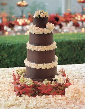 Brown five layer cake with roses and grapes