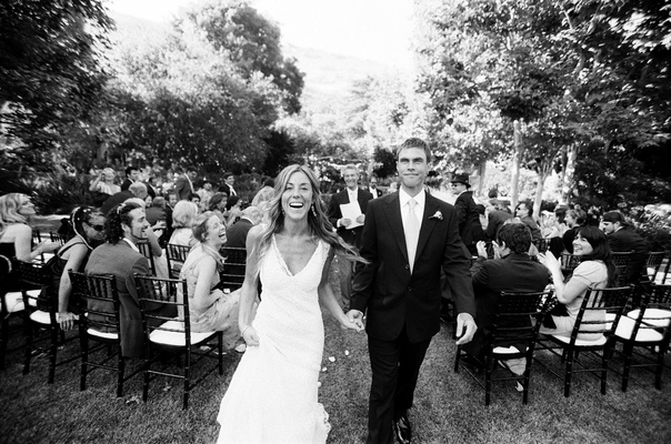 Black and white photo of a bride in a Monique Lhuillier gown and a groom in a black tuxedo and tie