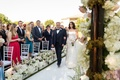 Bride walking down aisle with father of bride white boxes along aisle with white hydrangeas and rose