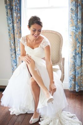 Bride in a Lela Rose lace gown puts on Stuart Weitzman heels with lace details
