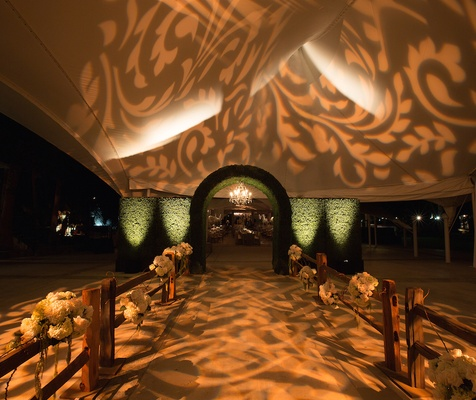 Reception tent entrance with green hedges and lighting