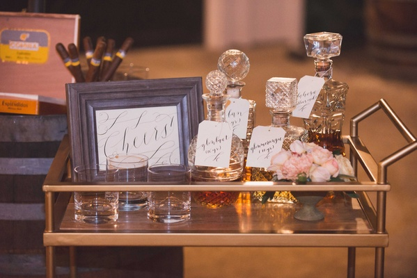 Gold bar cart with cheers calligraphy print crystal decanters filled with alcohol liquor glasses