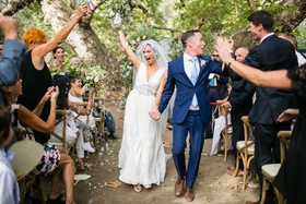 Bride in Jenny Packham wedding dress and groom in navy blue suit hold hands up wedding ceremony