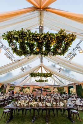 wedding reception greenery ceiling installations with glass orbs candles white drapery tent wood
