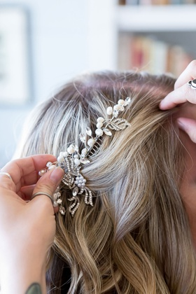 bride with lightly curled blonde hair hairstylist putting in comb pearl rhinestone crystal details