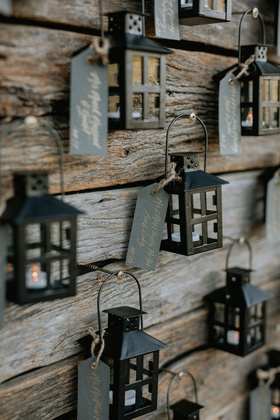 wedding reception escort card display reclaimed wood wall black lantern with tag place card