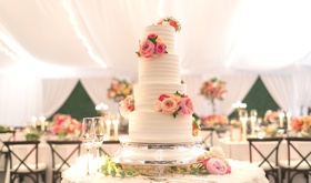 four-tiered wedding cake with horizontal frosting layers and fresh flowers