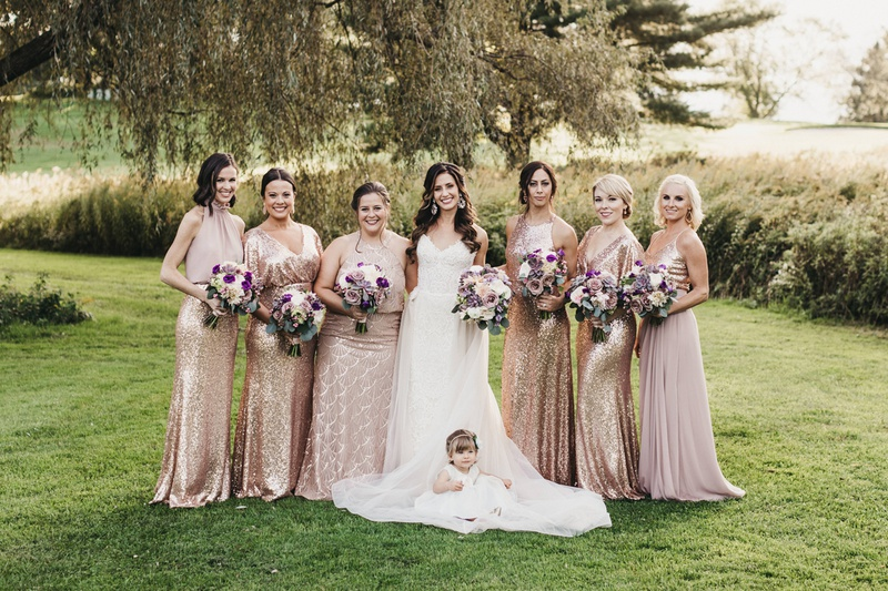 bride in nicole spose gown in center of bridesmaids in rose gold sequins, flower girl in front