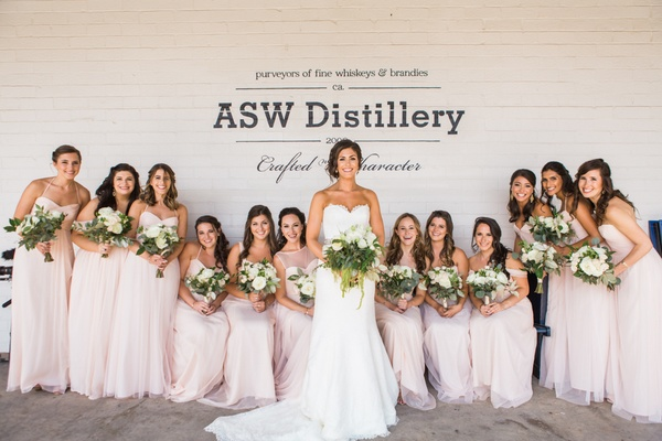 bride and bridesmaid hold bouquets blush dresses