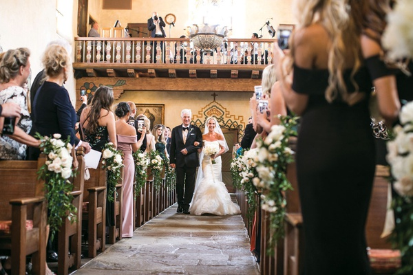 bride and her father at the back of aisle with church pews decorated with greenery and white flowers