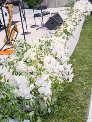 outdoor white stage for live band lined with cascading white orchids and greenery