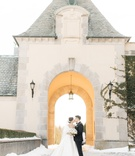 bride in ball gown with white fur wrap veil low bun kiss groom in arch of oheka castle snow ground