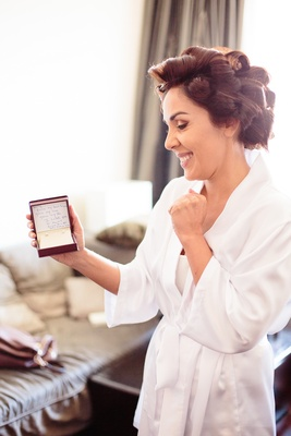 Bride in a white robe and curlers receives diamond stud earring from groom on wedding day
