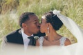 African American and Filipino bride and groom kissing