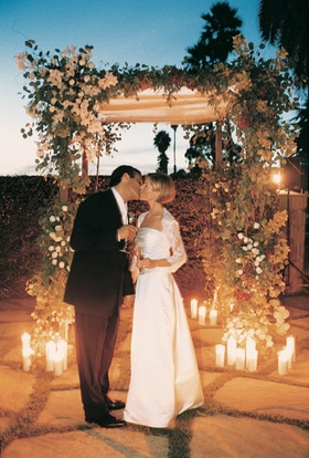 Couple in front of chuppah decorated with flowers