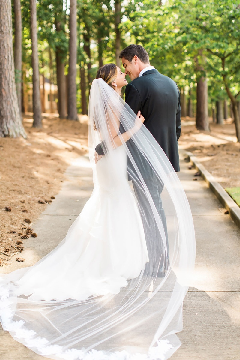 Couple portrait in wooded area forest camp with sheer veil and lace trim hem