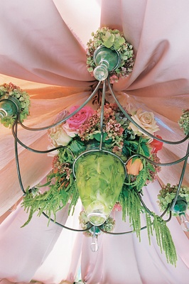 chandelier covered in green vines and pink flowers