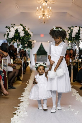 two flower girls in white dresses with baskets and greenery white flower crowns white aisle petals