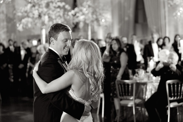 Black and white photo of groom in tuxedo dancing with bride in a strapless dress
