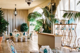 Wedding reception cocktail hour lounge tropical beach theme with blue decor wicker chairs ottomans
