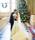 Bride and groom hug in front of Christmas tree