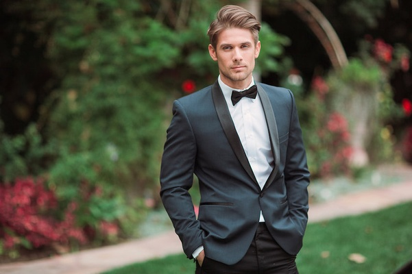 Groom wears dark blue tuxedo jacket with black pants and bow tie, Eden Gardens, CA