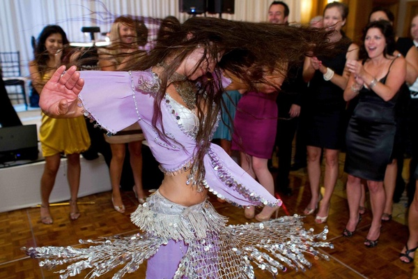 Woman belly dancing in purple and silver costume