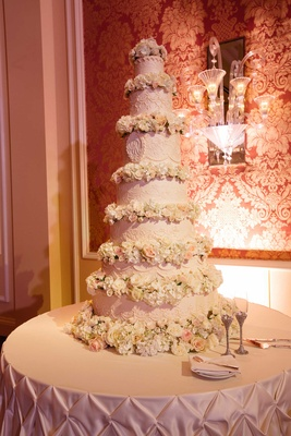 Seven tier traditional wedding cake with flowers between each tier and monogram in center