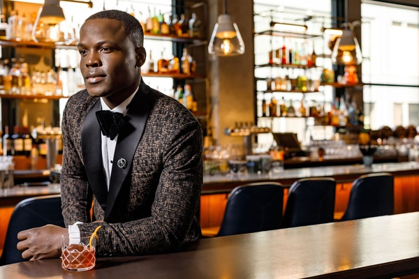 Groom in pattern tuxedo jacket black lapel with bow tie pin and cocktail at bar in chicago