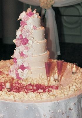Pink florals cascade down wedding cake