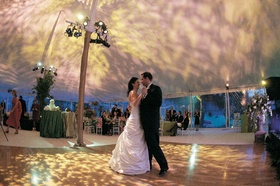 Bride in a Pnina Tornai gown dances with a groom in a black tuxedo
