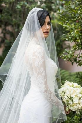 Bride holding white bouquet in sweetheart neckline wedding dress with long sleeve illusion bolero