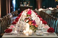 long wedding reception table with small floral arrangements and pillar candles down the center