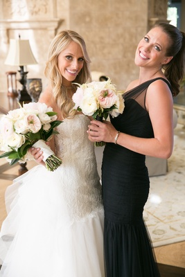 Bride in bridal suite with girlfriend in asymmetrical dress