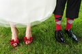 Bride in red patent leather Valentino heels and groom in black Salvatore Ferragamo dress shoes