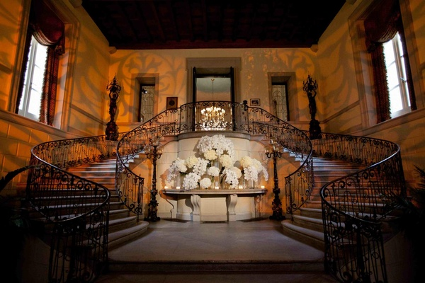 Grand staircase with wrought iron railing at Oheka Castle