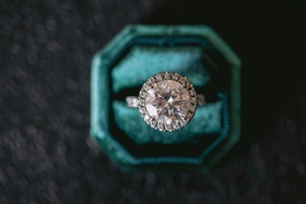 wedding ring engagement ring in velvet teal ring box large round diamond halo setting