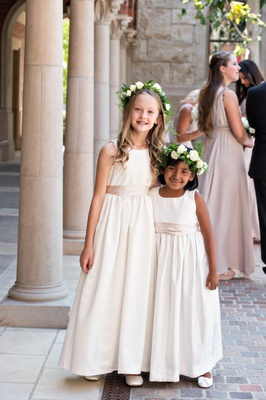 two flower girls with long ivory dresses and taupe sashes, flower crowns