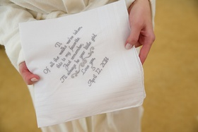 Bride holds handkerchief with grey embroidery