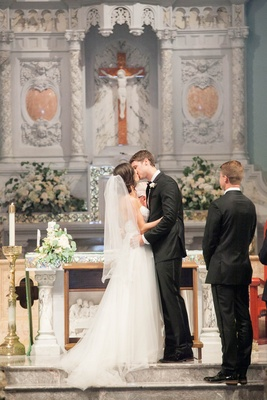 bride and groom kiss at the altar of their Catholic ceremony